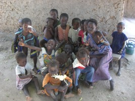 group of children near adobe hut